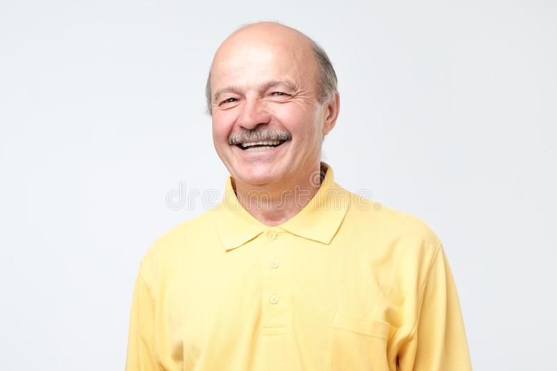 Mature adult man laughing looking at the camera over white background. Mature adult man in yellow shirt with moustache laughing looking at the camera over white royalty free stock photos