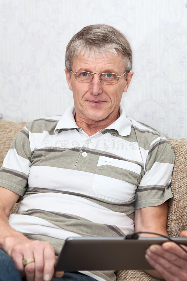Download Mature Adult Working With Tablet Computer At Domestic Sofa Stock Photo - Image: 32872668