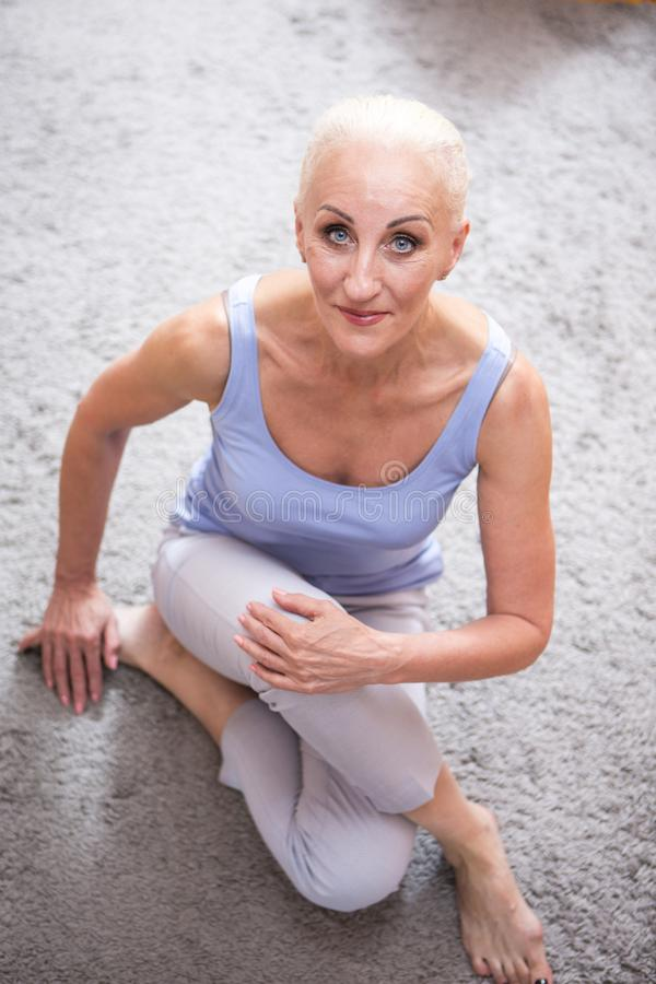 Senior Adults Concepts. Portrait of Positive Caucasian Blond Senior Woman Posing in Casual Clotthing. Sitting on Floor with folded royalty free stock photos