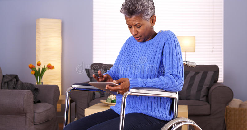 Mature African woman sitting in wheelchair with tablet royalty free stock image