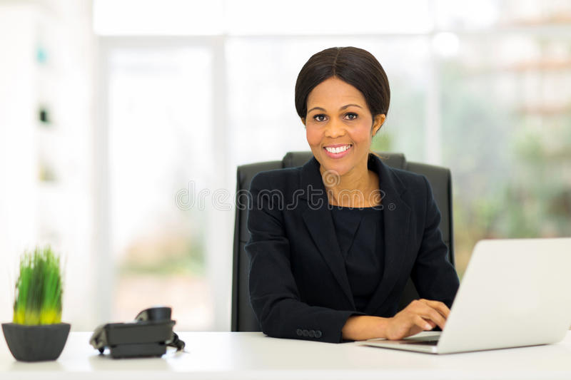 Mature afro business woman. Attractive mature afro american business woman using computer in office royalty free stock photo