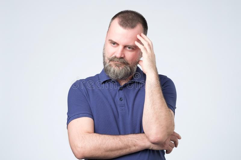 Mature age, problem and people concept. Bearded man in blue clothes thinking royalty free stock photography