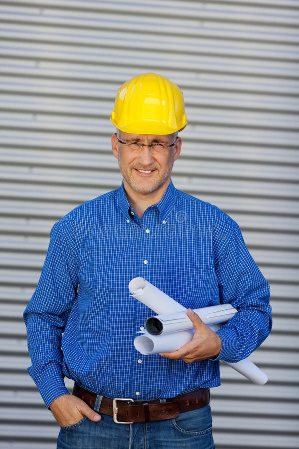Mature Architect Holding Blueprints Against Shutter royalty free stock images