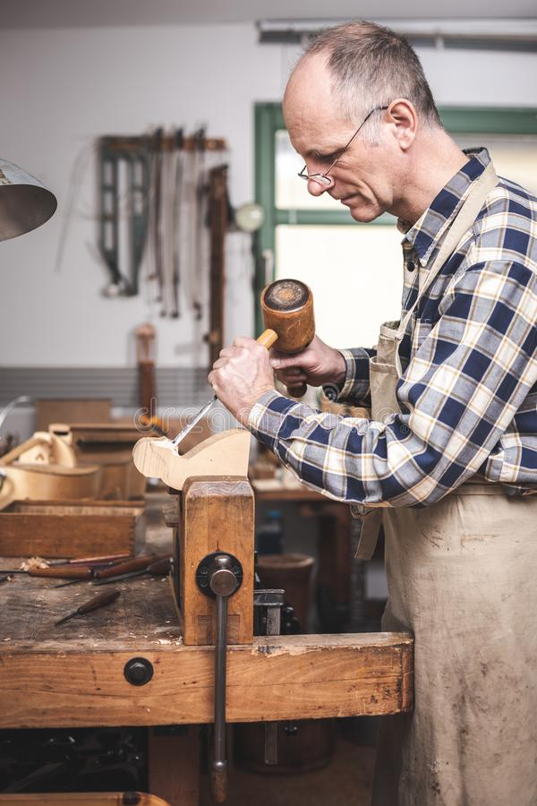 Experienced artisan focused on carving a piece of wood. Mature artisan carving a wooden figure at a rustic workbench. He is using a chisel and mallet royalty free stock photos
