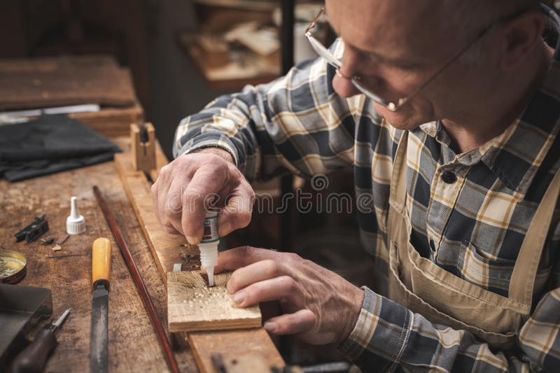 Experienced craftsman working on a workbench. Mature artisan sitting at a rustic workbench while carefully applying glue on a small item. ed on the task. He is stock photography