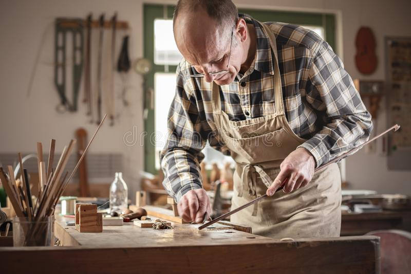 Mature artisan working in a workshop. Instrument builder in a rustic workshop. He is focused on a violin bow sanding it down manually royalty free stock photo