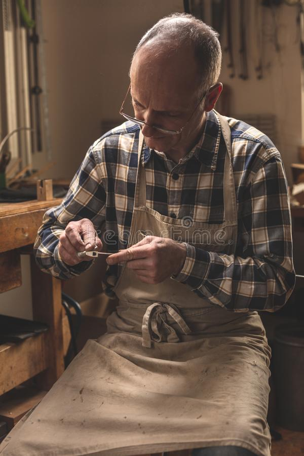 Experienced instrument builder in a rustic workshop. Mature artisan in a workshop manually sanding down a violin bow. He is wearing an old apron and a checkered royalty free stock photography