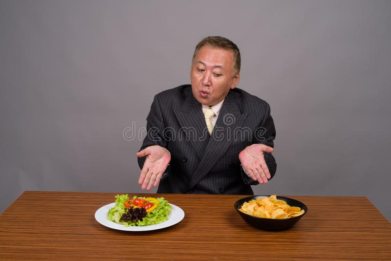 Mature Asian businessman sitting with wooden table against gray. Studio shot of mature Asian businessman sitting with wooden table against gray background stock photo