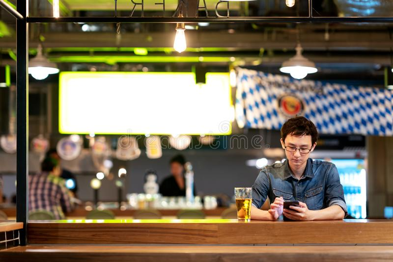 Mature asian chinese man with tired and thoughful face sitting at counter bar, pub or restaurant drinking beer looking at smartpho stock images
