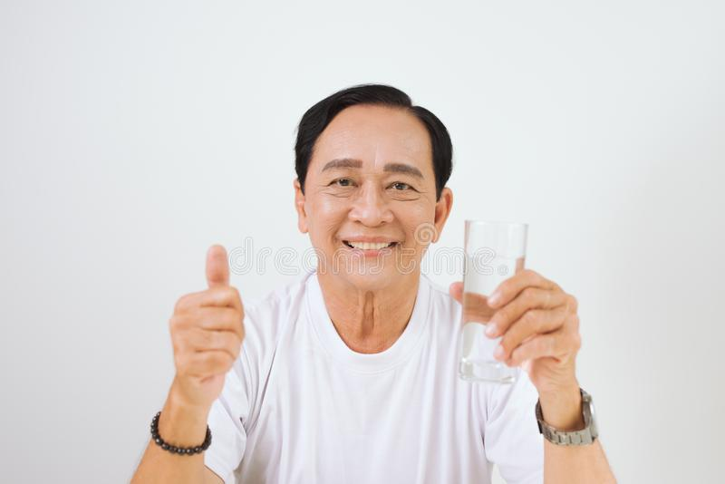 Mature asian man showing thump up with a glass royalty free stock photo