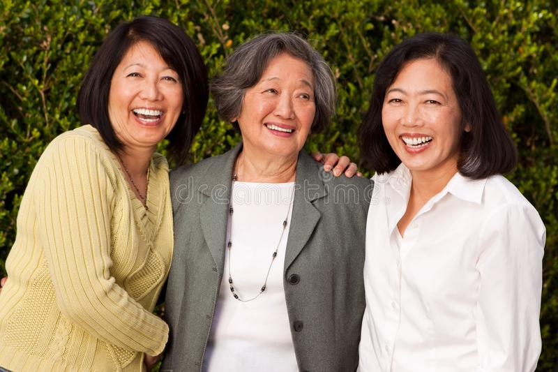 Mature Asian mother and her adult daughters. royalty free stock images
