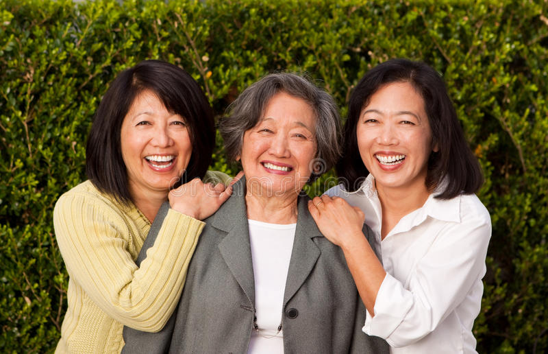 Mature Asian mother and her adult daughters. stock photo