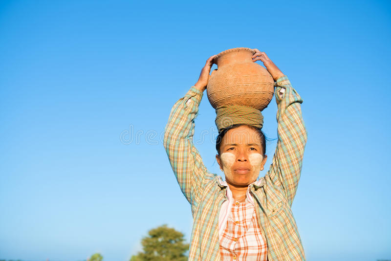 Mature Asian traditional female farmer carrying clay pot on head stock images