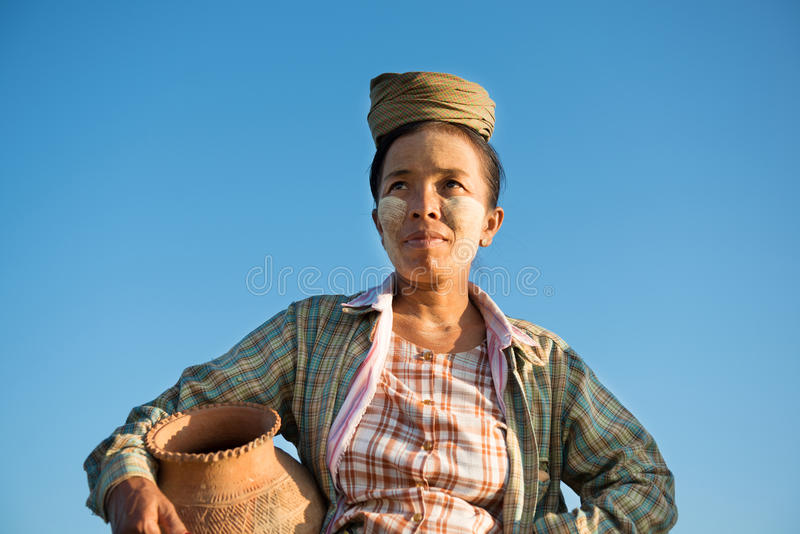 Mature Asian traditional female farmer carrying clay pot stock images