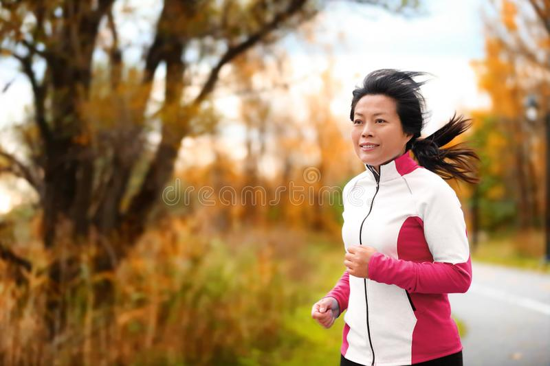 Mature Asian woman running living active lifestyle. Mature Asian woman running active in her 50s. Middle aged female jogging outdoor living healthy lifestyle in stock photos