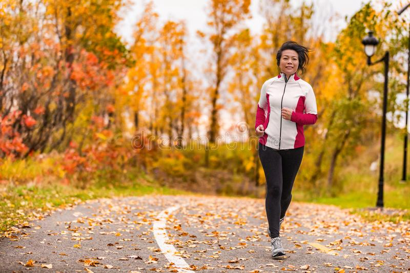 Mature Asian woman running living healthy lifestyle. Mature Asian woman running active in her 50s. Middle aged female jogging outdoor living healthy lifestyle in stock image