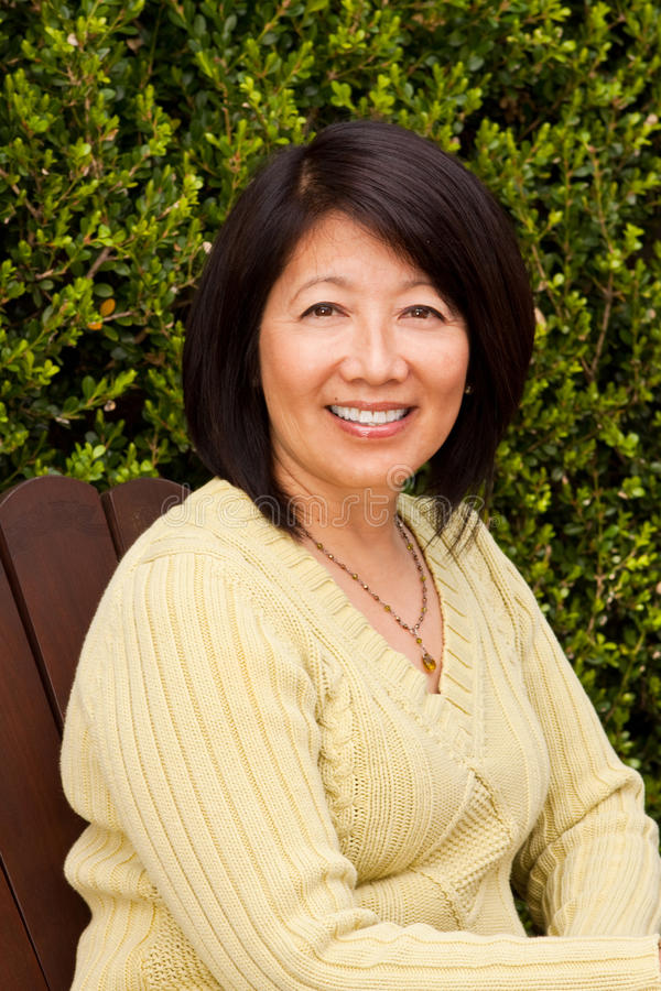Mature Asian woman smiling sitting outside. royalty free stock photography