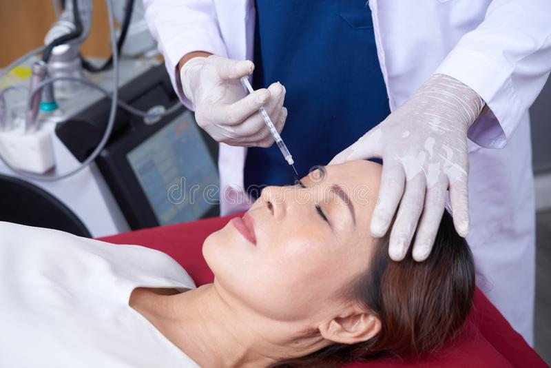 Botox injection. Mature Asian women getting botox injection at beauty salon stock images