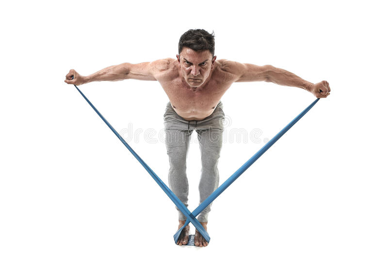 Mature athletic sport man with bodybuilder strong and fit body training doing exercises with elastic rubber band royalty free stock photos