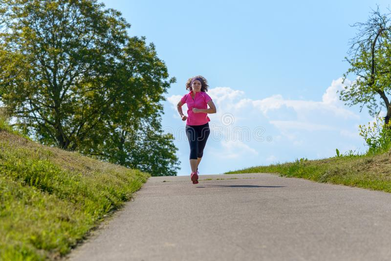 Mature athletic woman jogging on a rural road royalty free stock photography