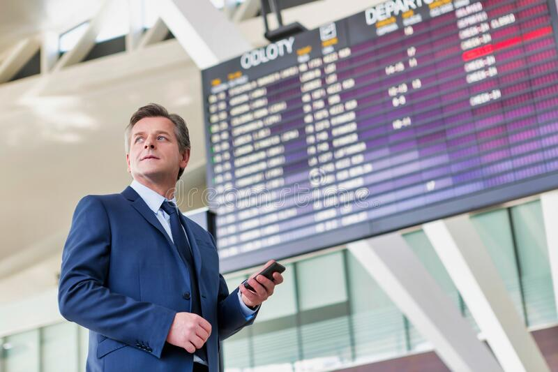 Mature attractive businessman using smartphone while standing against flight display screen in airport. Photo of Mature attractive businessman using smartphone stock photography