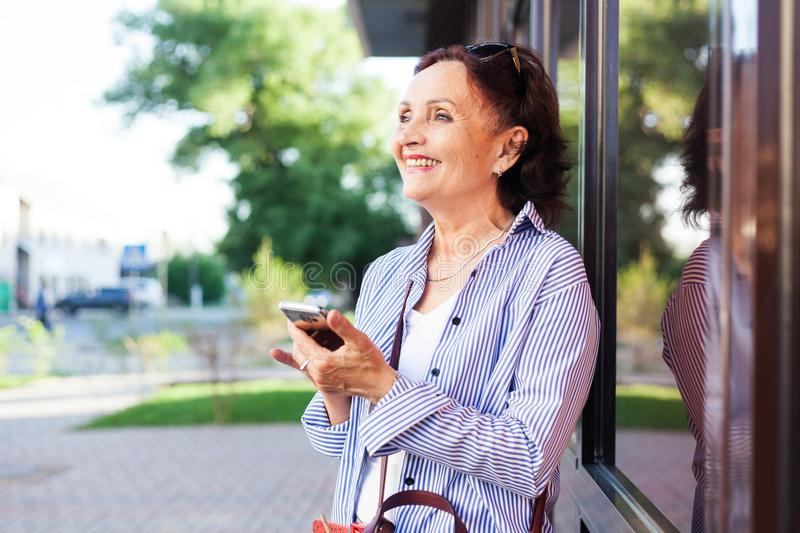 Mature attractive stylish woman retired using mobile phone app royalty free stock photo