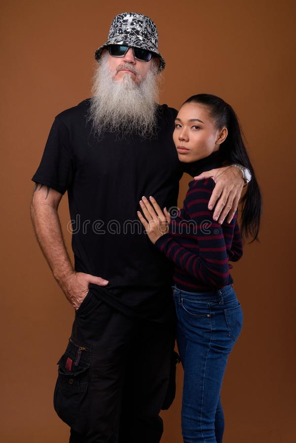 Mature bearded bald man with young Asian transgender woman stock images