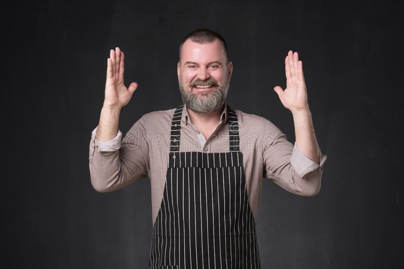 Mature bearded man in apron bragging about the big size of something. royalty free stock photo