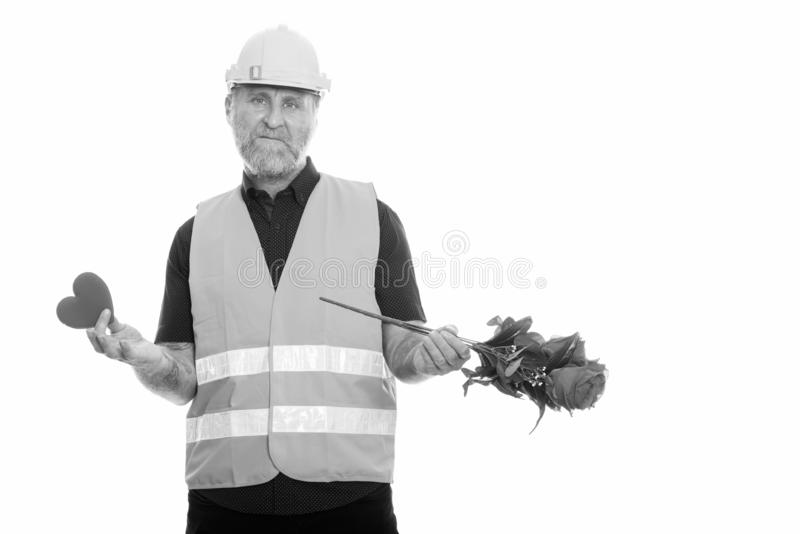 Mature bearded man construction worker ready for Valentine`s day. Studio shot of mature bearded man construction worker isolated against white background in stock images