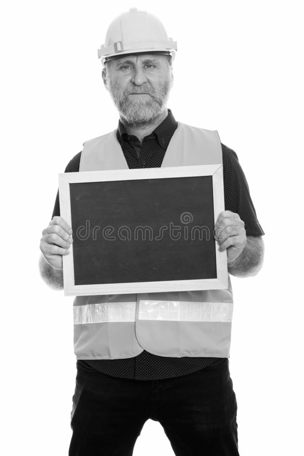 Mature bearded man construction worker showing blackboard. Studio shot of mature bearded man construction worker isolated against white background in black and royalty free stock photo