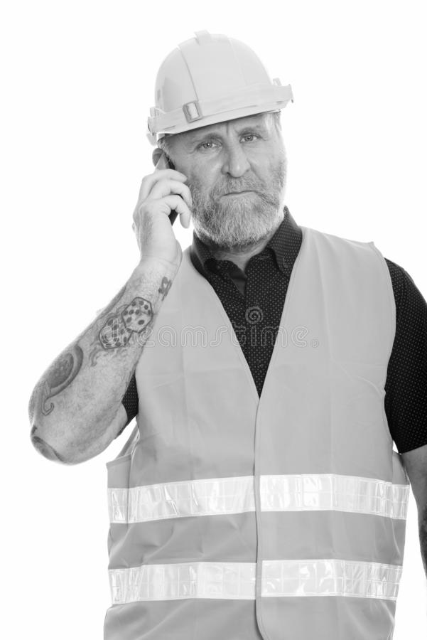 Mature bearded man construction worker talking on the phone. Studio shot of mature bearded man construction worker isolated against white background in black and royalty free stock image