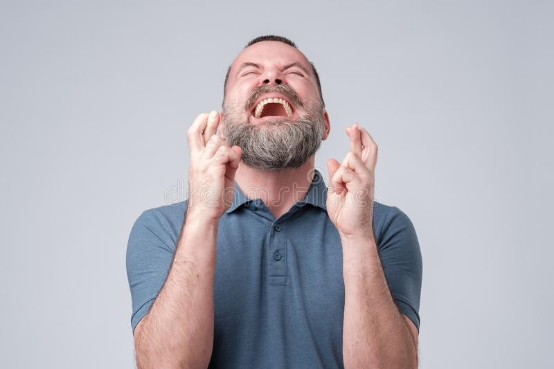Mature bearded man crossing fingers and closed eyes, asking for good luck. stock photo