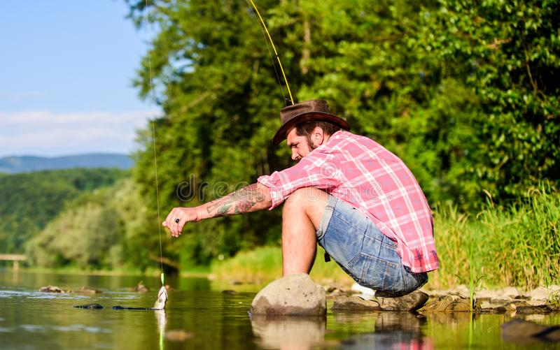Mature bearded man with fish on rod. big game fishing. relax on nature. fly fish hobby. Summer activity. successful royalty free stock photography