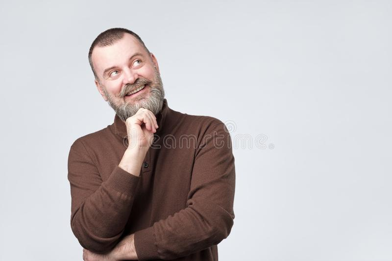 Mature bearded man looking up and thinking about future. stock images