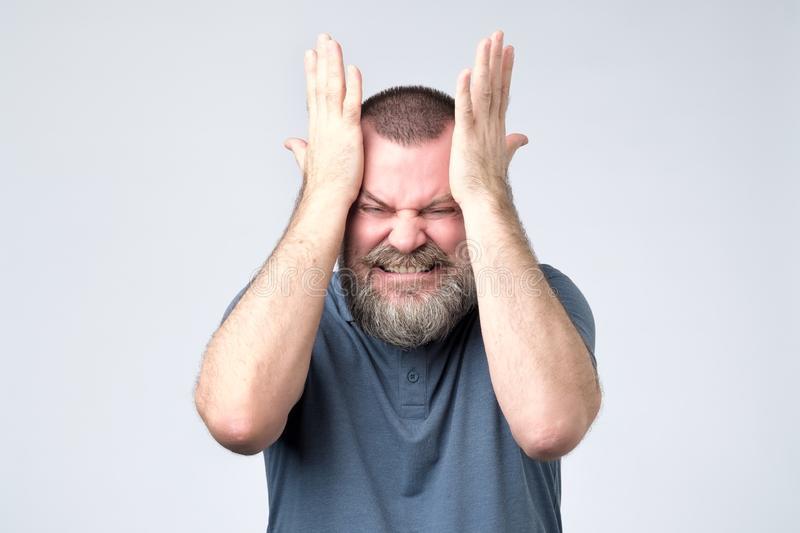 Mature bearded man standing and clenching head from a migraine attack stock photo