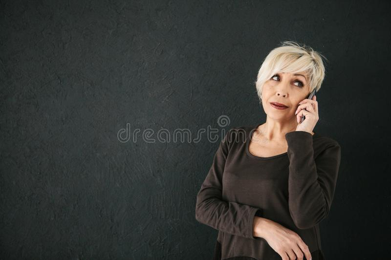 Mature beautiful positive woman talking on cell phone. A successful positive elderly female consultant is negotiating a cell phone. Communication between people stock images