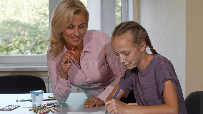 Mature beautiful woman enjoying drawing with her little student royalty free stock images