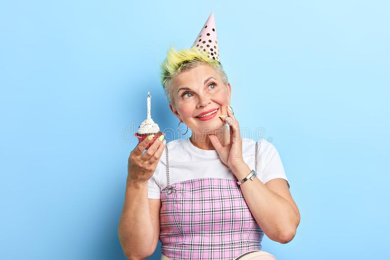 Mature beautiful woman holding a birthday cake, touching her cheek, looking up. Dreaming about love, happiness. isolated over blue background royalty free stock photo