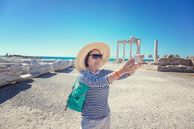 Mature beautiful woman traveler takes pictures on mobile phone. royalty free stock photo