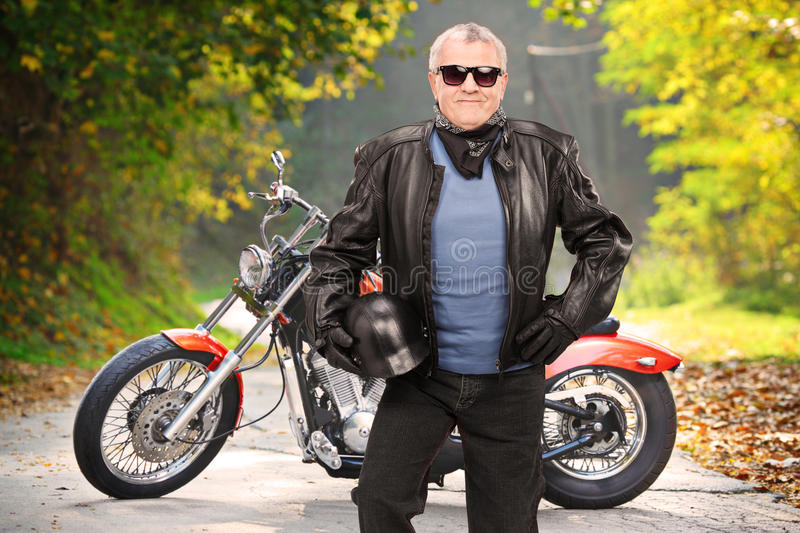 Mature biker in leather jacket standing in front of his chopper stock image