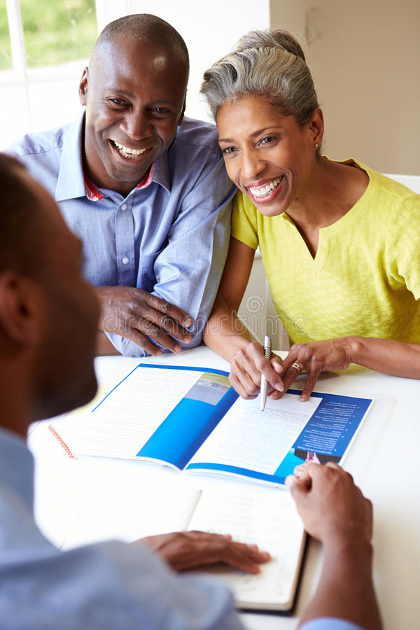 Mature Black Couple Meeting With Financial Advisor At Home. Discussing Documents Smiling At Each Other