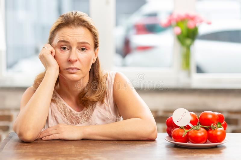 Mature blond-haired woman sitting at the table having food allergy. Food allergy. Mature blond-haired woman sitting at the table having food allergy and feeling stock photography