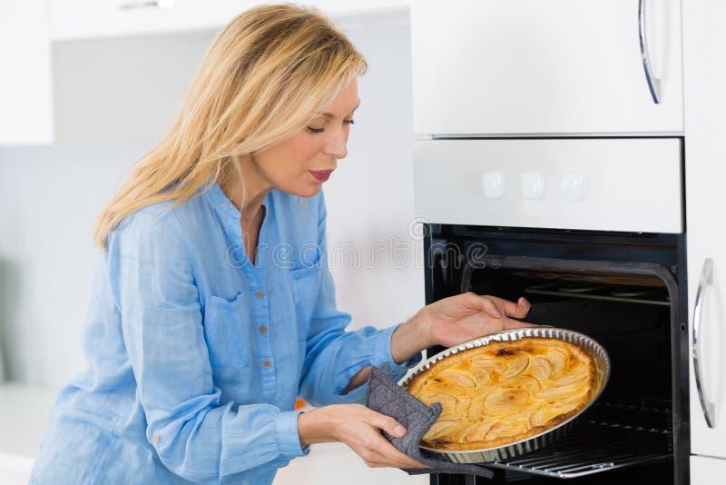 Mature blond woman baking tart in oven stock photos