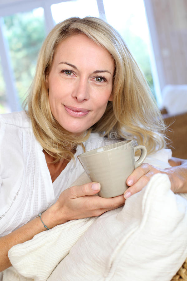 Mature blond woman with cup of tea royalty free stock photos