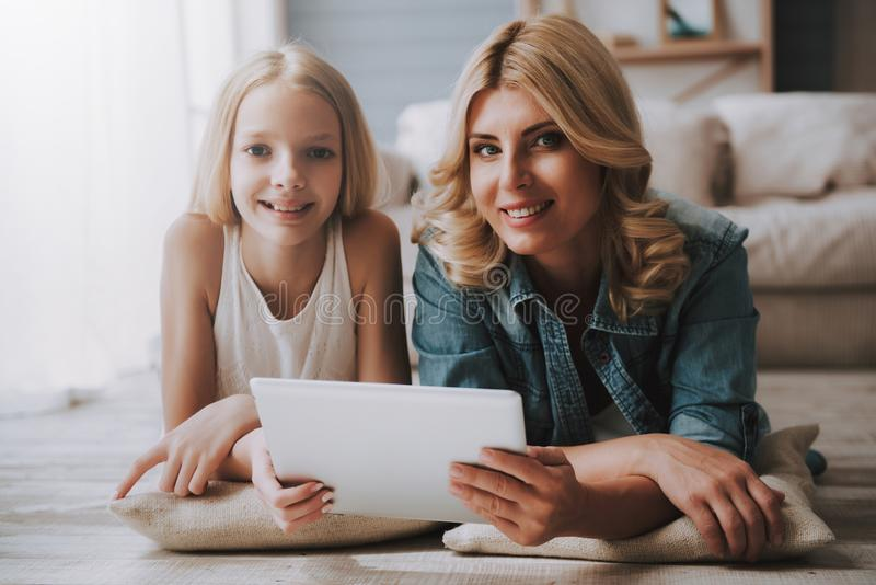 Mature blond woman with cute daughter watching tablet while lying on floor. stock photos