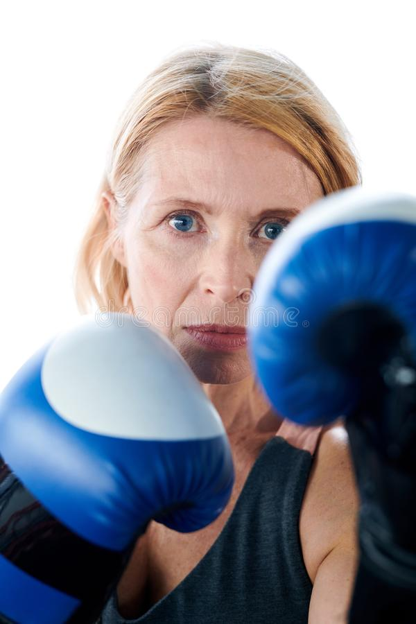 Dangerous boxer. Mature blonde boxer in blue leather boxing gloves concentrating on fight while looking at her rival ready to kick stock photos