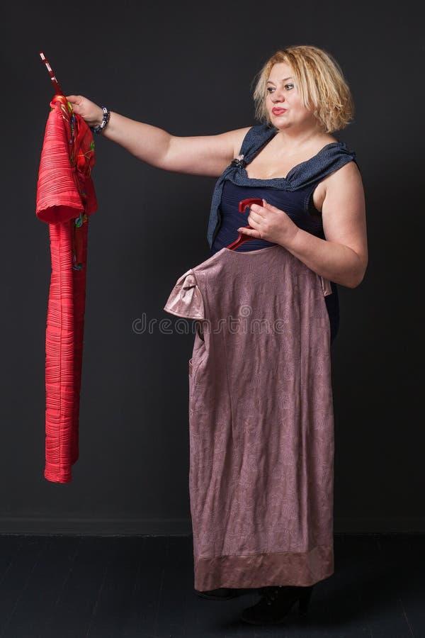 Mature blonde woman choosing dress royalty free stock images