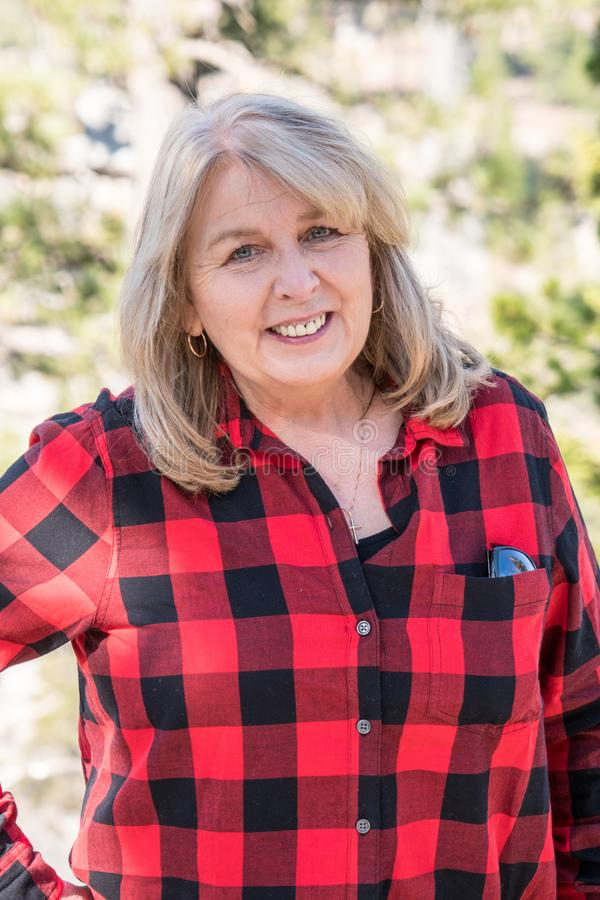A mature blonde woman wearing a buffalo plaid flannel shirt red and black poses for a portrait in the Eastern Sierra Nevada royalty free stock photography