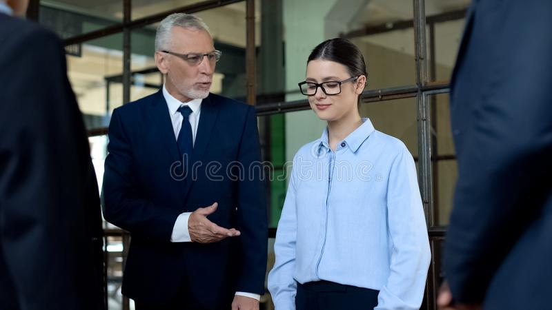 Mature boss introducing new female colleague in office, career promotion stock images