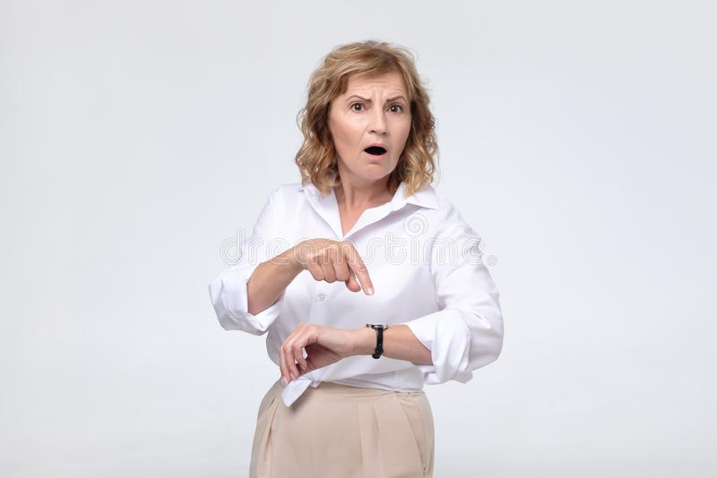 Mature boss woman is angry because of her coworker being late. She is showing time on her watch. Concept of irritation of dead line royalty free stock image